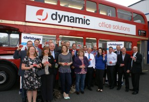 Chamber Patron members with their model red buses in front of a converted showroom bus.